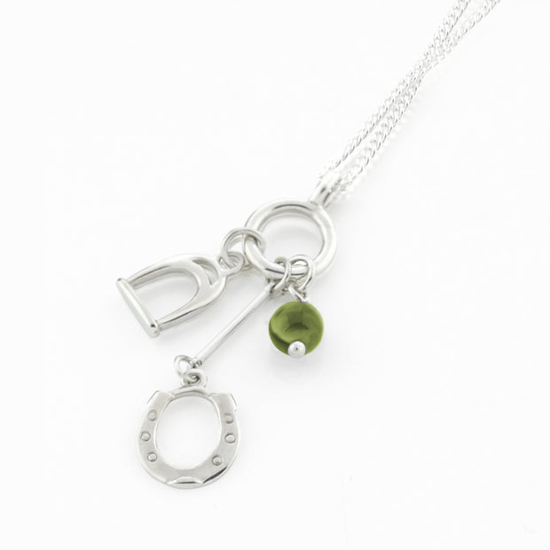Designer solid silver horseshoe, stirrup and peridot charm necklace on white background