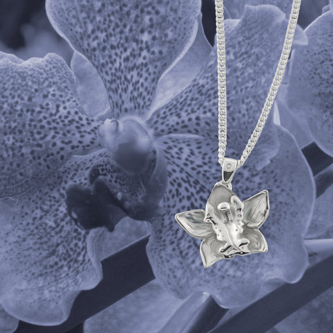 solid silver carved orchid necklace in front of purple image of orchid