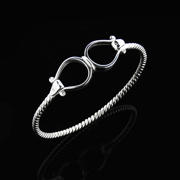 Solid silver double western stirrup opening bangle on black.