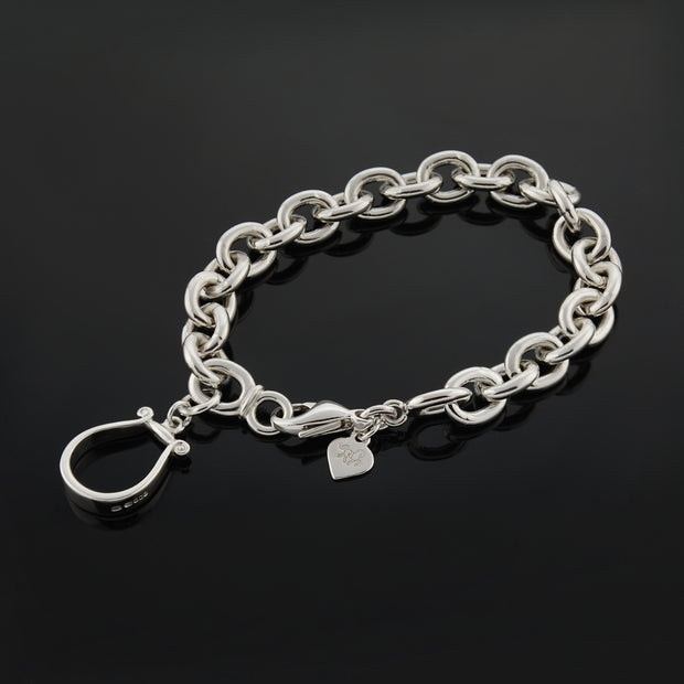 Designer solid silver western stirrup heavy chain bracelet on black background.