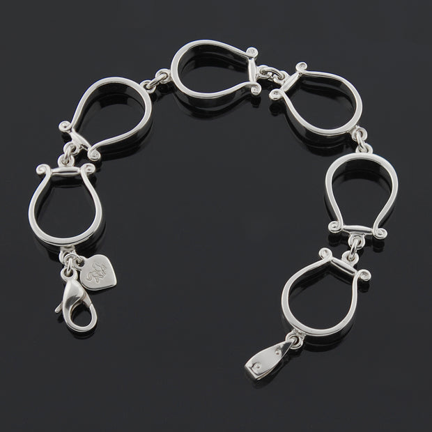 Designer six western stirrup solid silver bracelet on black background.