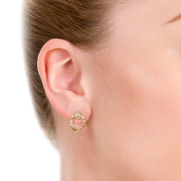 Close up image of model wearing designer solid 9ct gold horseshoe stud earrings on white background.