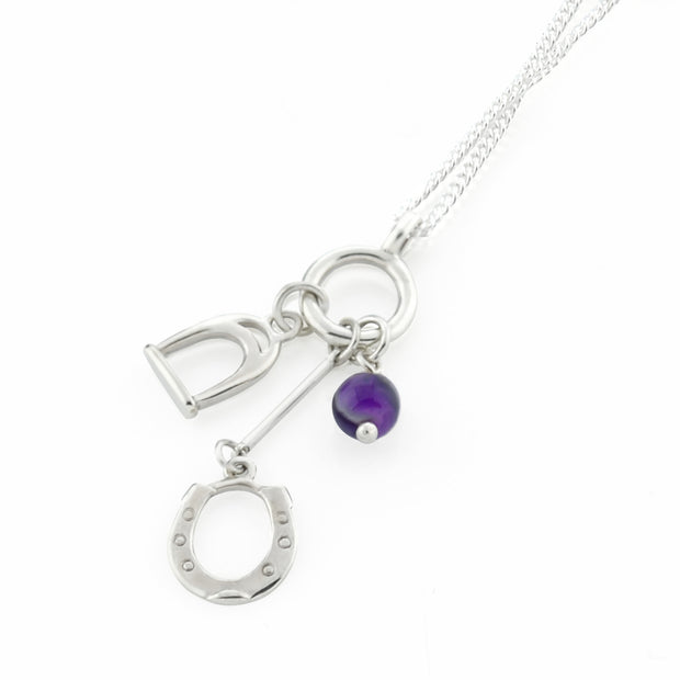 Designer solid silver horseshoe, stirrup and amethyst charm necklace on white background.