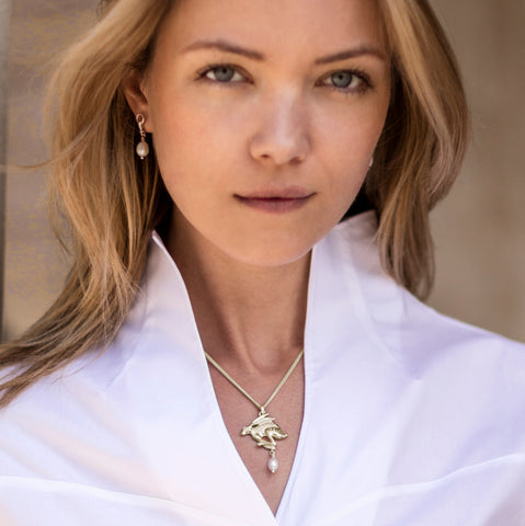 Blonde young woman wearing solid silver carved hare with a cultured pearl drop necklace