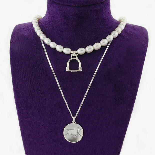 Designer Horse coin and badminton pearl necklaces on dark purple display bust.