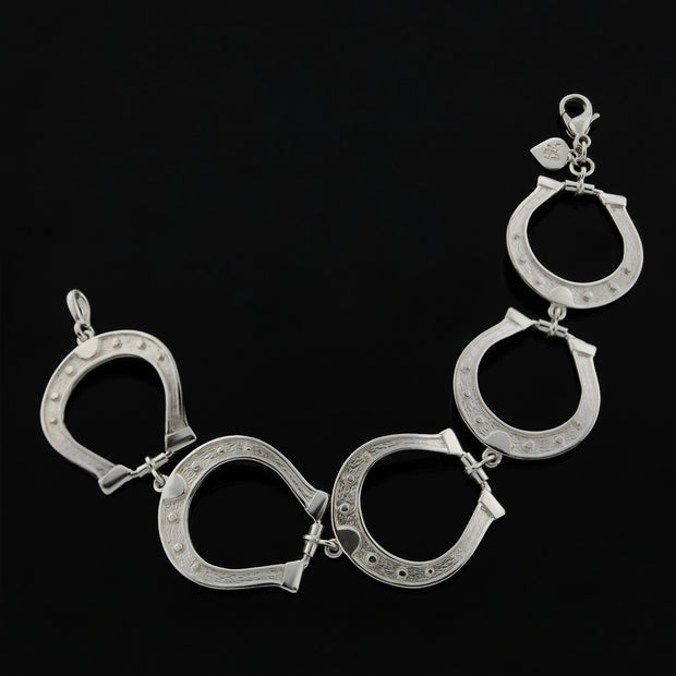 Designer solid silver large horseshoe bracelet on black background.