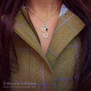 Charlotte wearing Designer solid silver horseshoe, stirrup and amethyst charm necklace with tweed.
