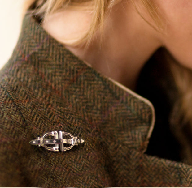 model wearing tweed and designer solid silver stirrup and strap brooch/stockpin