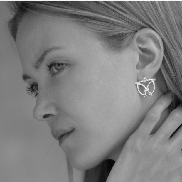 model wearing olid silver designer wrought iron inspired earrings on white background.