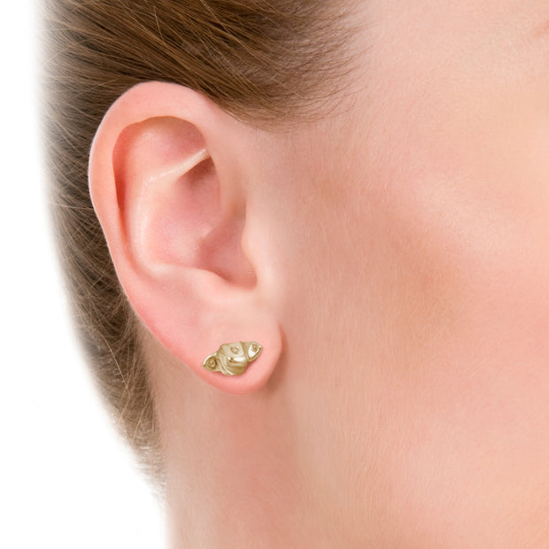 close up of model wearing designer gold knotted strap stud earrings on white background.
