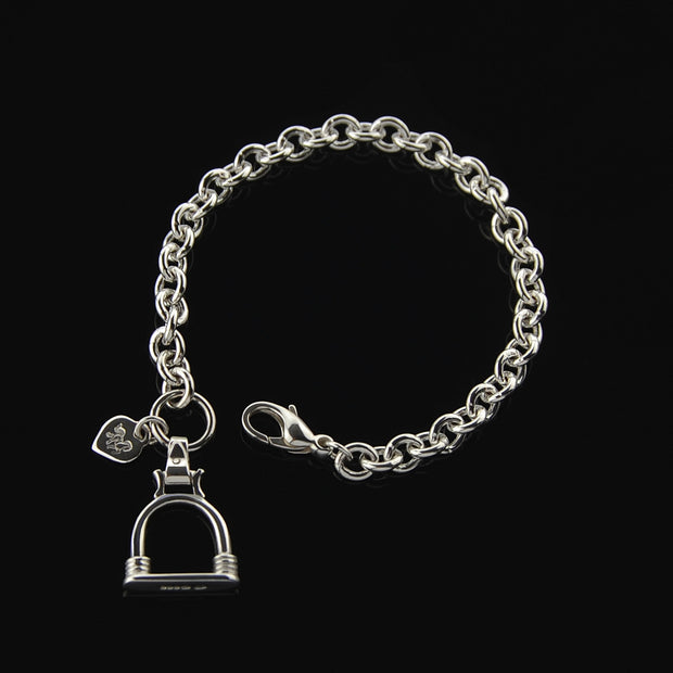 Designer solid silver heavy weight chain bracelet with vintage stirrup inspired large charm on black background.