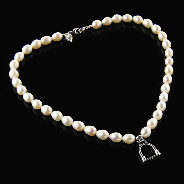 designer cultured pearl necklace with vintage solid silver stirrup design charm on black background.