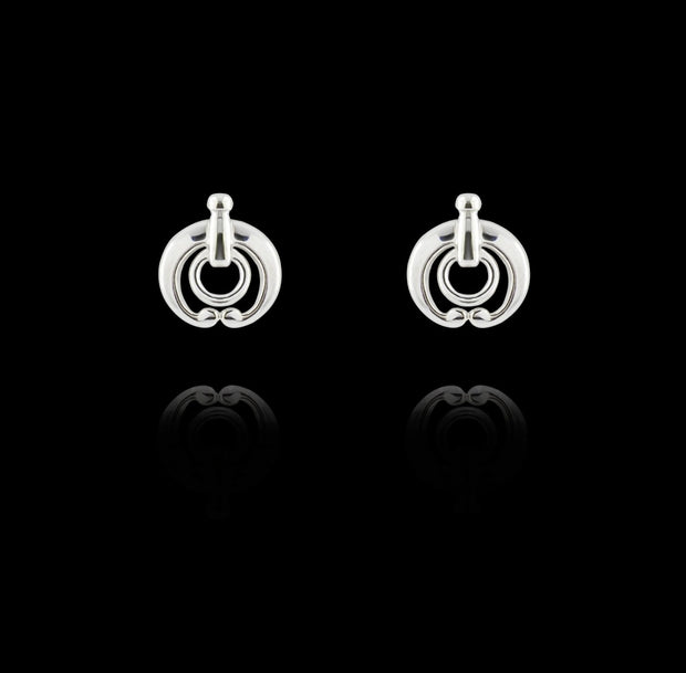 designer silver equestrian stud earrings on black background