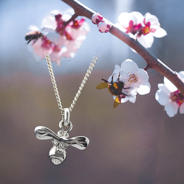 designer silver carved honey bee necklace on apple blossom background