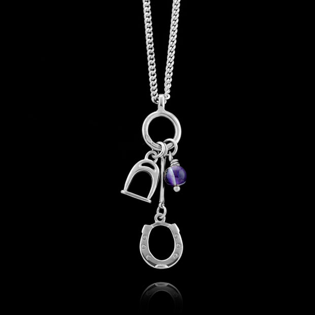 Designer solid silver horseshoe, stirrup and amethyst charm necklace on black background.