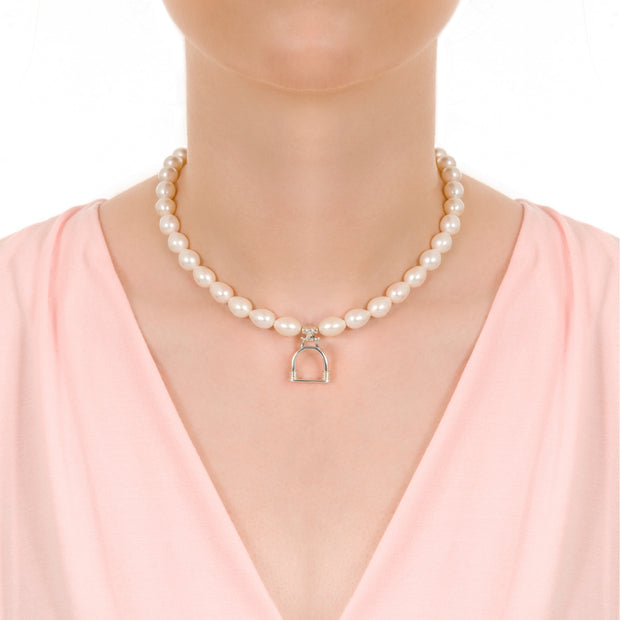 close up of model's neck wearing designer cultured pearl necklace with vintage solid silver stirrup design charm on white background.