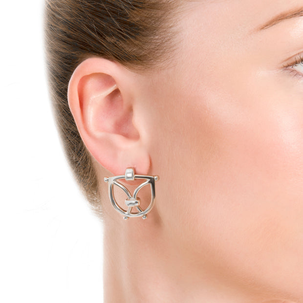 close up image of model wearing olid silver designer wrought iron inspired earrings on white background.