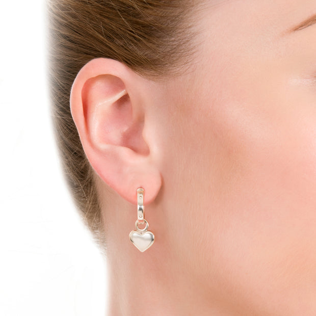ear shot of model wearing designer solid silver leather strap hoops with removable heart drop earrings on white background.