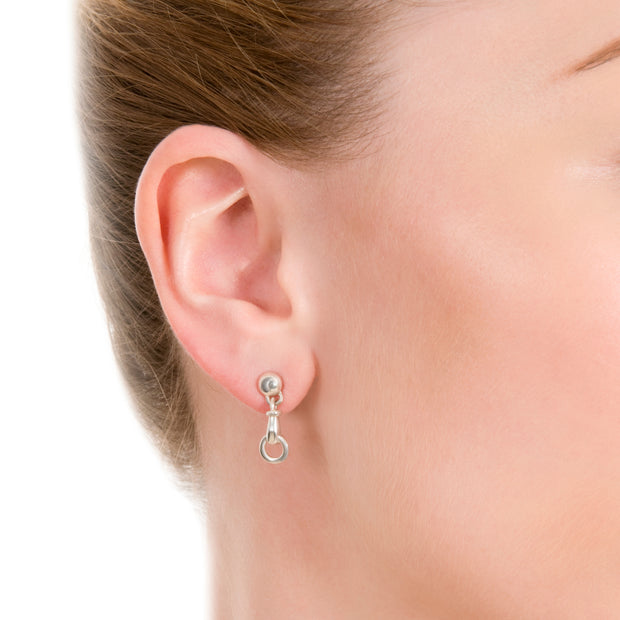 close up shot of model wearing designer solid silver windsor horsebit drop earrings on white background