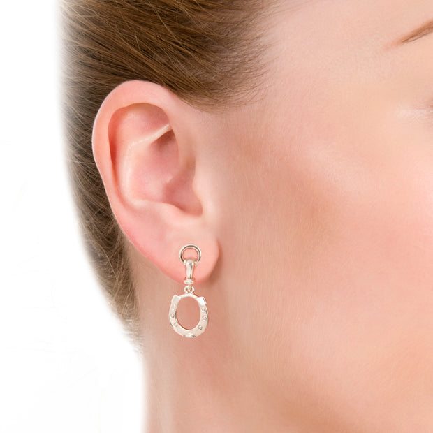 close up shot of model wearing designer solid silver horseshoe drop earrings with bit top detail on white background