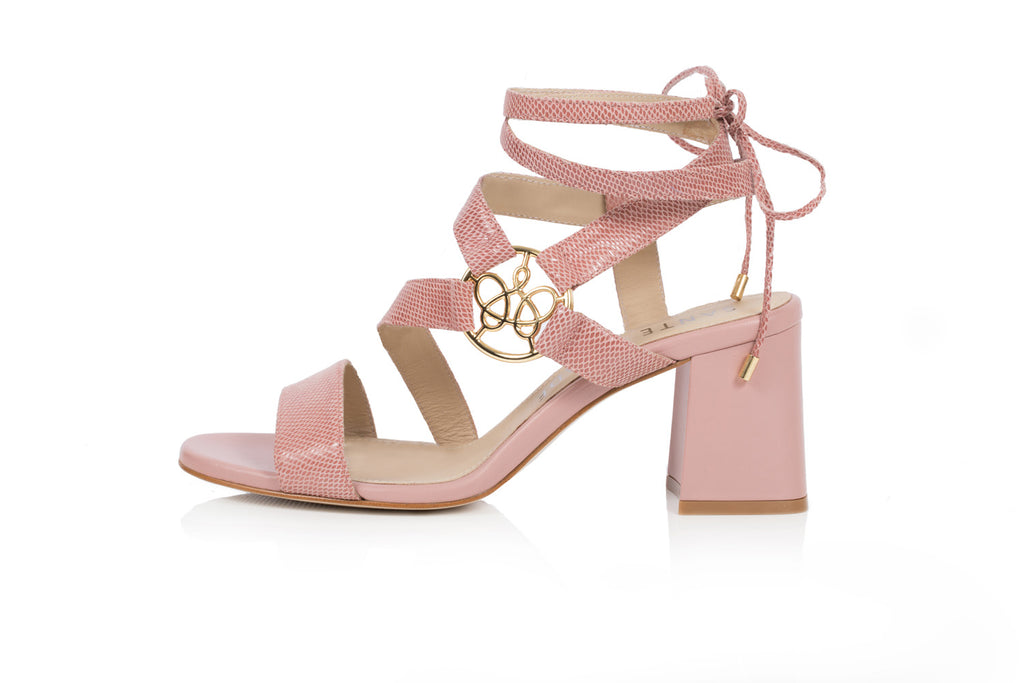 Embossed leather ankle-tie sandal with asymmetric straps and gold logo ornament, set on 65mm flared block heel