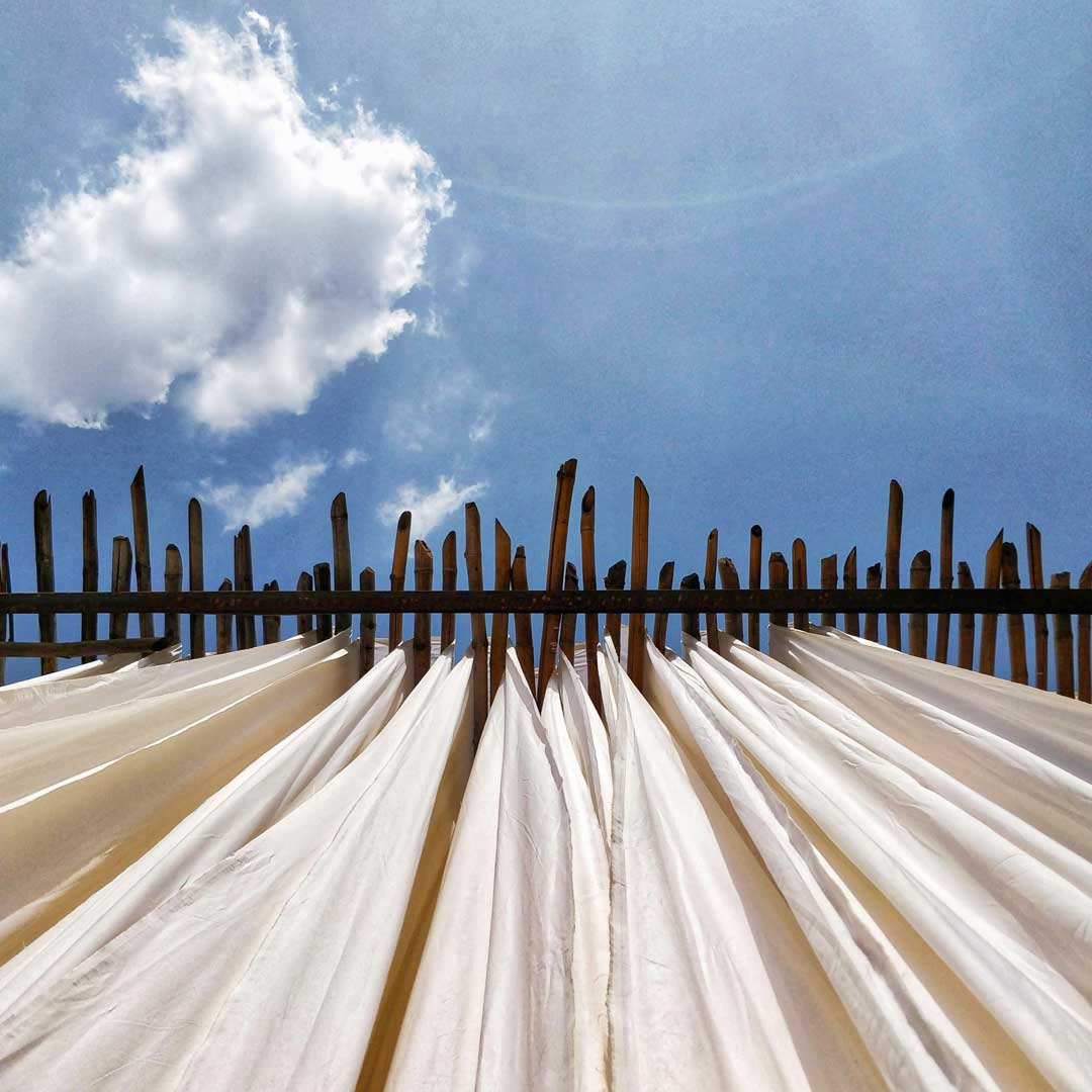 a 2 point perspective shot from below of Kora Khadi fabric hang drying in the sun under a clear blue sky. The picture a slight flare and a small clour in top left half.