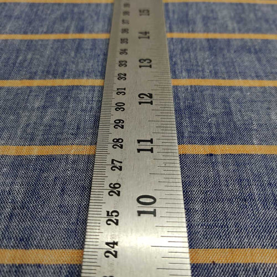 A perspective  shot of a steel measuring scale lying blue cotton khadi fabric with orange stripes.
