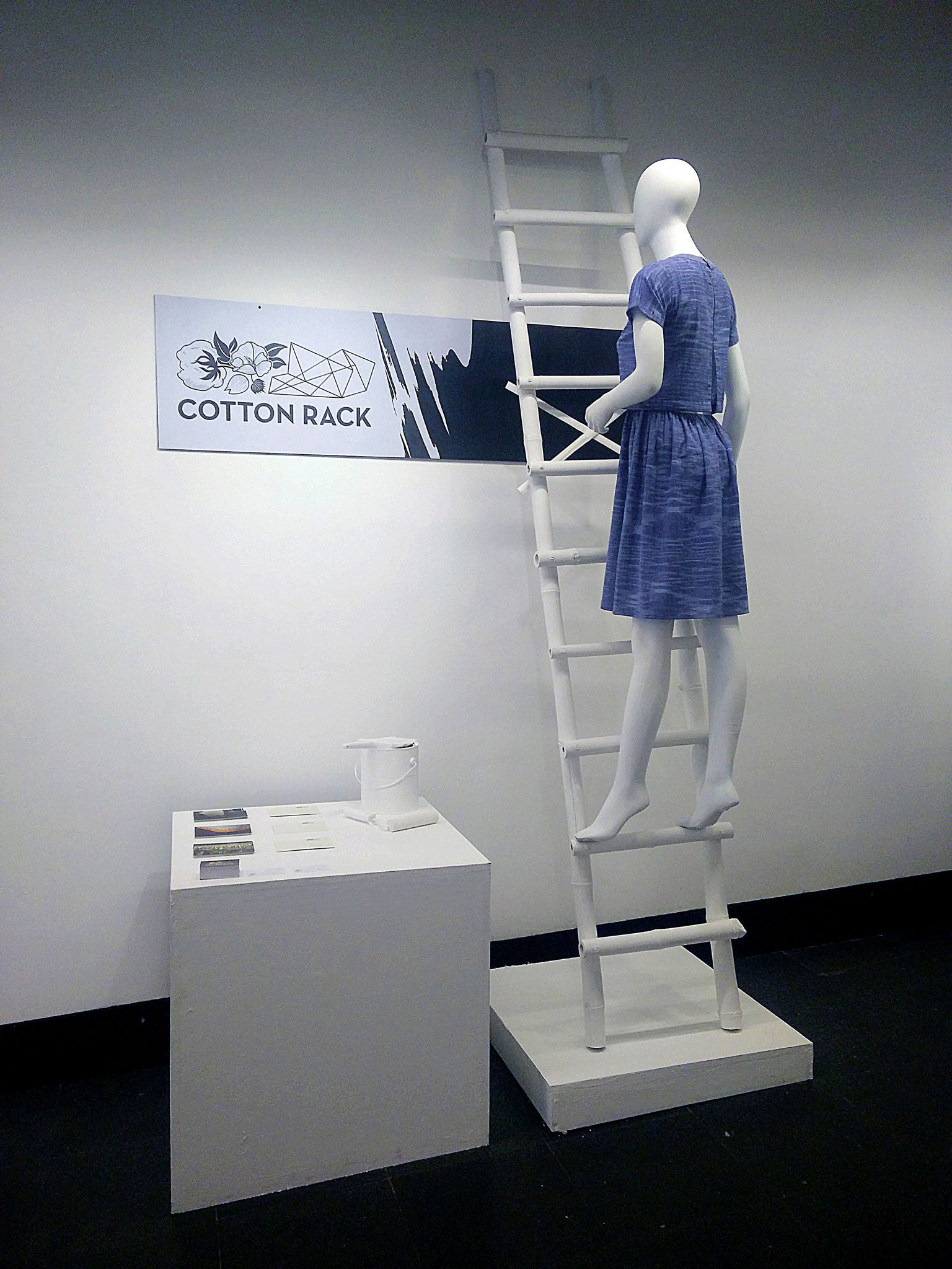 An installed made for 20 Under 35, Delhi where a white female mannequin dressed in blue Cotton Rack Khadi dress is climbing white wooden stairs to paint the Cotton Rack banner