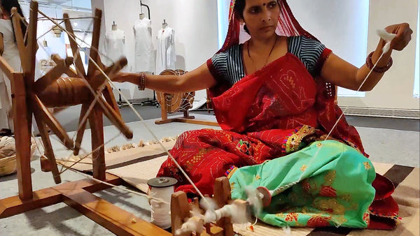 A Rajasthani women clad in bandhini saree sitting on ground and spinning cotton yarn (soot) on a Gandhi Charkha (Indian Spinning Wheel)