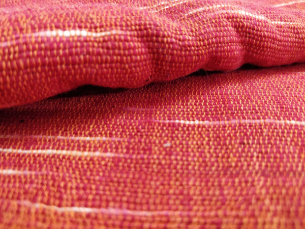 Uneven Space Dyed Red-Orange Khadi fabric by Cotton Rack also known as Jharna or Upkar Shirting in India