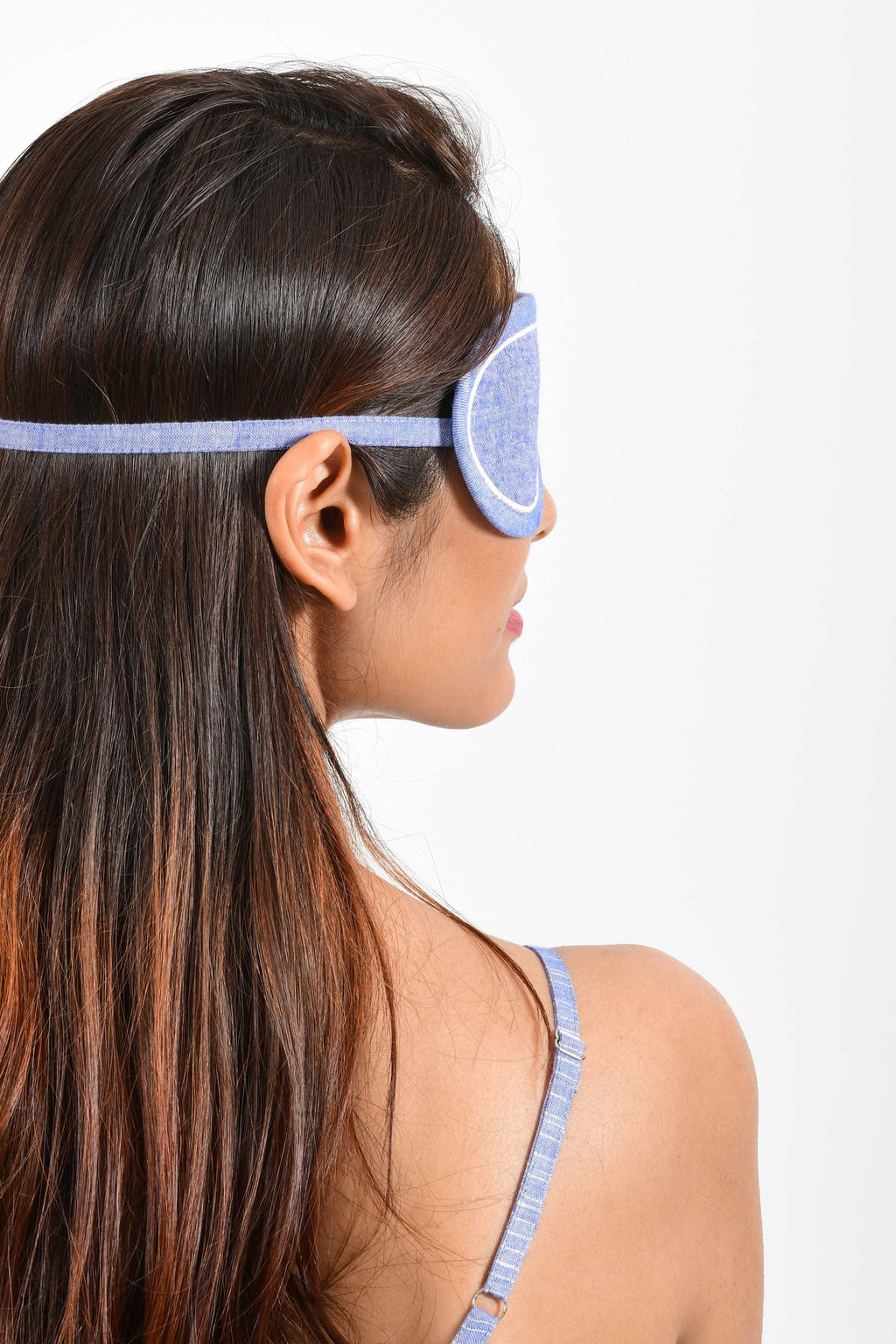 Back portrait of an Indian female womenswear fashion model wearing a blue chambray handspun and handwoven khadi cotton eye mask by Cotton Rack.
