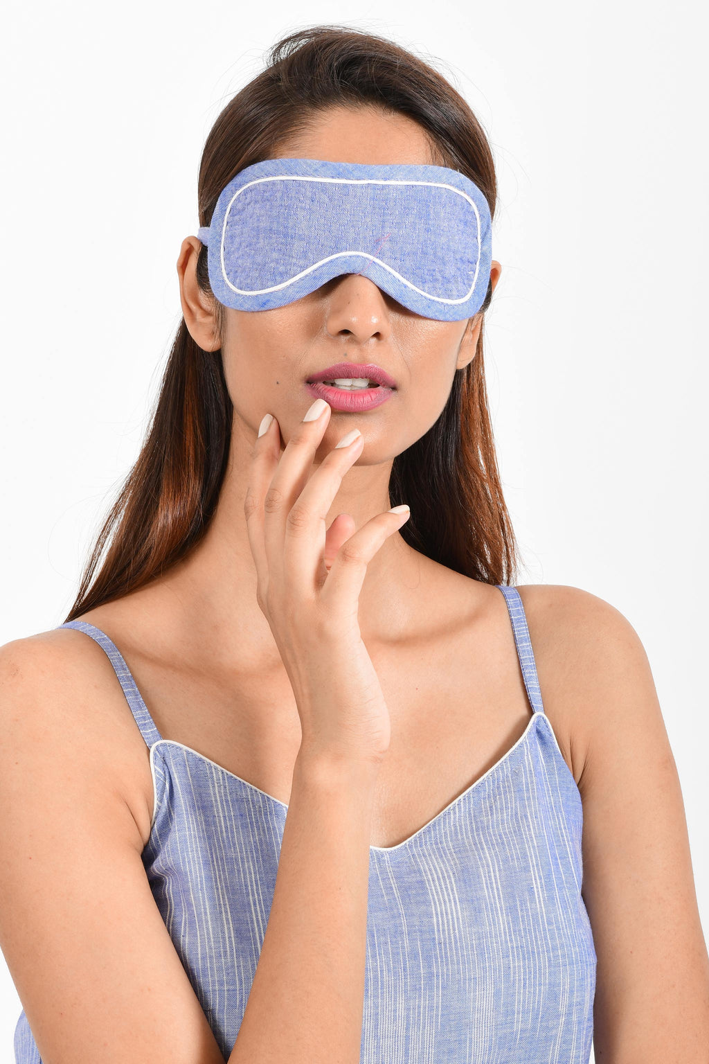 Front portrait of an Indian female womenswear fashion model wearing a blue chambray handspun and handwoven khadi cotton eye mask by Cotton Rack.