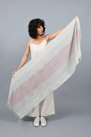 A womeswear fashion Model holding a minimally designed homespun handwoven fine khadi cotton stole by Cotton Rack with an overall metal block print, in red, blue and black checks at centre and stripes