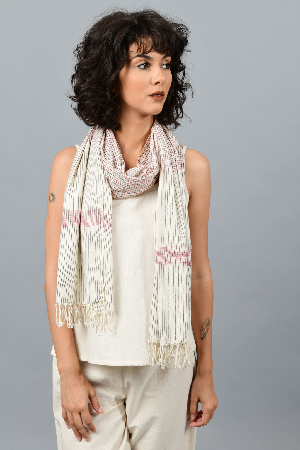 A female womenswear fashion Model wearing a minimally designed off-white homespun and handwoven fine khadi cotton stole by Cotton Rack printed with read and blue stripes around her neck