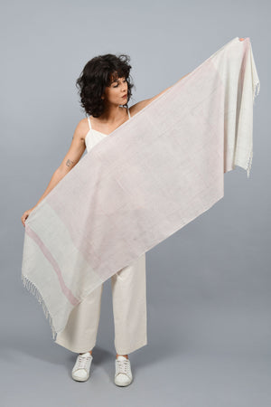 Model holding and showing off an off-white homespun and handwoven fine cotton stole printed with read and blue stripes