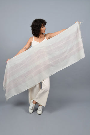A female womenswear fashion Model holding a minimally designed homespun handwoven fine Khadi cotton stole by Cotton Rack with an overall metal block printed in red, blue stripes inspired by agnes martin