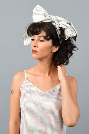 front of a model wearing a bandana tied as bow on the head printed with fine blue stripes using brass block over handspun handwoven khadi cotton from maheshwar