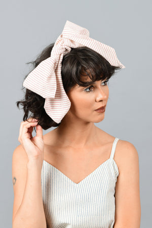 front of a model wearing a bandana tied as bow on the head printed with fine red stripes using brass block over handspun handwoven khadi cotton from maheshwar