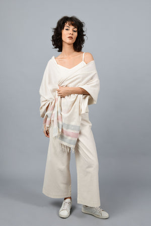 A female womenswear fashion Model posing wrapped in a minimally designed homespun handwoven fine Khadi cotton stole by Cotton Rack with an overall metal block printed in red, blue dots and stripes on an off-white base with spaghetti and palazzos