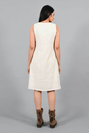 Back pose of an Indian female womenswear fashion model in an off-white Cashmere Cotton Pleated Dress made using handspun and handwoven khadi cotton by Cotton Rack.