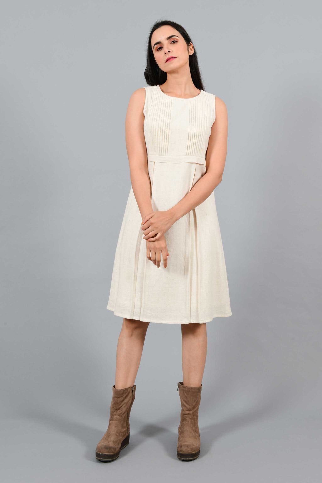 Stylised front pose of an Indian female womenswear fashion model in an off-white Cashmere Cotton Pleated Dress made using handspun and handwoven khadi cotton by Cotton Rack.