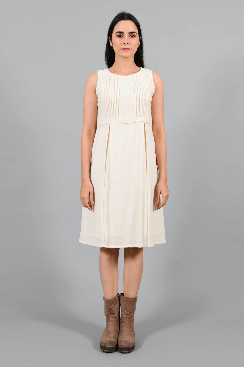 Front pose of an Indian female womenswear fashion model in an off-white Cashmere Cotton Pleated Dress made using handspun and handwoven khadi cotton by Cotton Rack.
