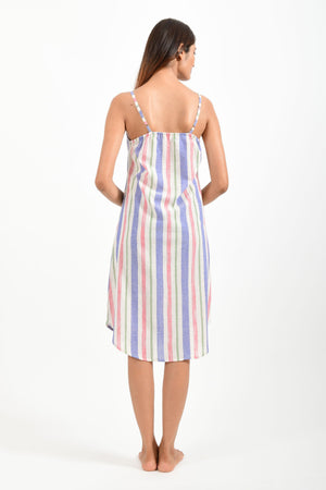 Back pose of an Indian female womenswear fashion model in an mutli colored striped handspun and handwoven khadi cotton spaghetti dress by Cotton Rack.