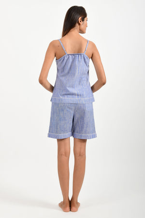 Back pose of an Indian female womenswear fashion model in azo-free space dyed blue handspun and handwoven khadi cotton spaghetti top and boxers by Cotton Rack.