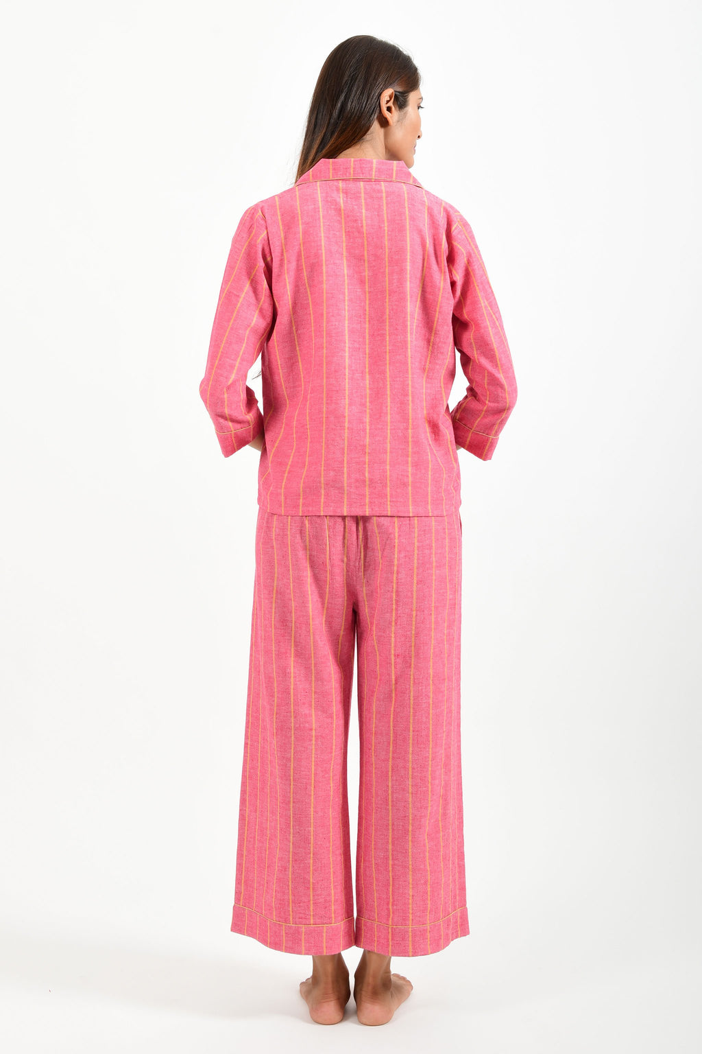 Back pose of an Indian female womenswear fashion model in azo-free dyed handspun and handwoven khadi cotton nightwear pyjama & shirt with red base and orange stripes by Cotton Rack.