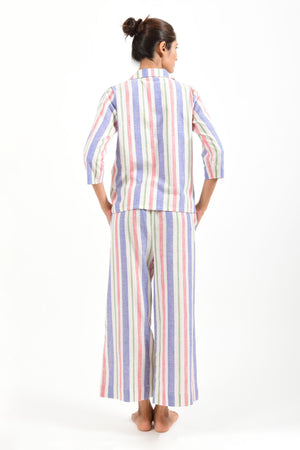 Back pose of an Indian female womenswear fashion model in a candy colored striped azo-free dyed handspun and handwoven khadi cotton nightwear pyjama & shirt by Cotton Rack.