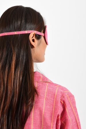 Back portrait of an Indian female womenswear fashion model wearing a red with orange stripe chambray handspun and handwoven khadi cotton eye mask by Cotton Rack.