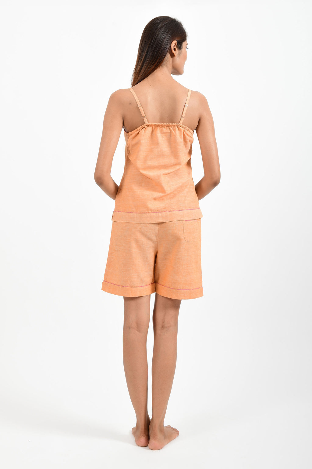 Back pose of an Indian female womenswear fashion model in azo-free dyed orange chambray handspun and handwoven khadi cotton spaghetti top and boxers by Cotton Rack.