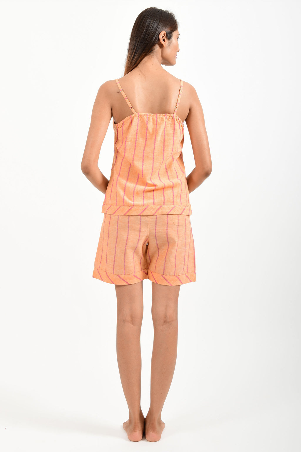 Back pose of an Indian female womenswear fashion model in azo-free dyed orange chambray (with red stripes) handspun and handwoven khadi cotton spaghetti top and boxers by Cotton Rack.