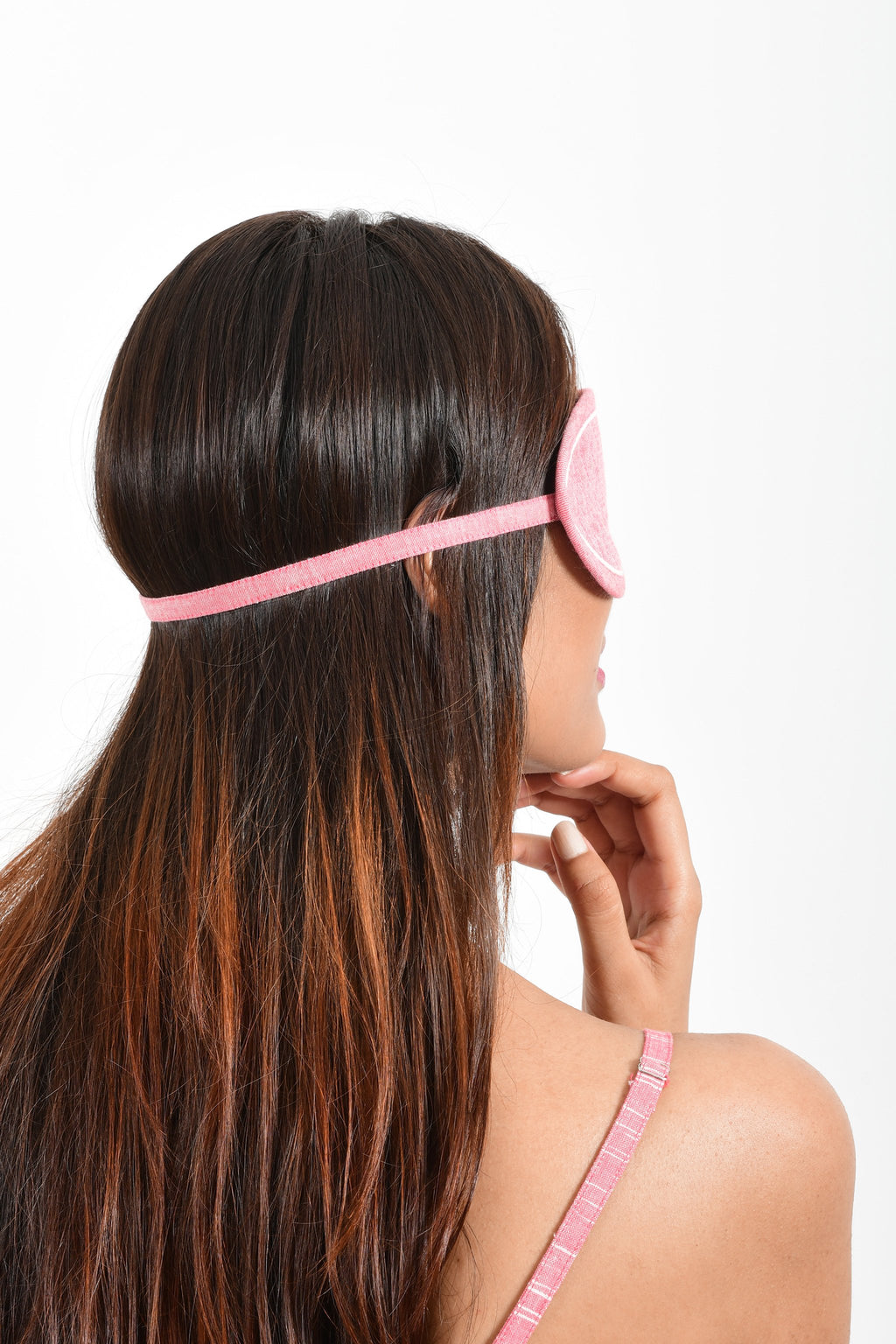 Back portrait of an Indian female womenswear fashion model wearing a pink chambray handspun and handwoven khadi cotton eye mask by Cotton Rack.